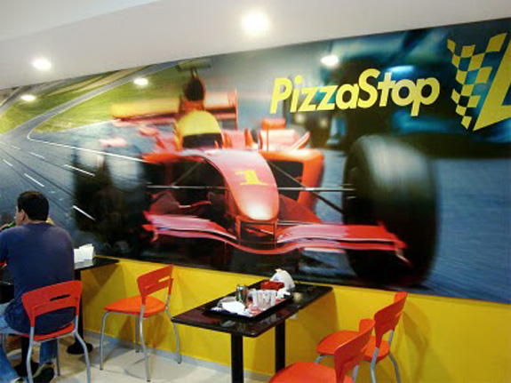 Fotos do automobilismo associadas à marca PizzaStop decoram o ambiente