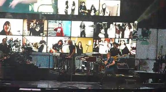 Vídeos no fundo do palco alternam diversas imagens inclusive closes de pessoas na platéia