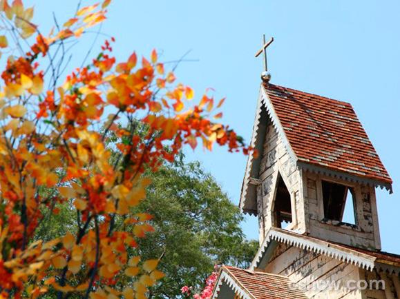 Torre da igreja recoberta de lata e árvore com tronco e galhos  recobertos com crochê colorido