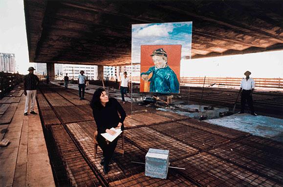 Lina Bo Bardi no vão livre do MASP ao lado dos cavaletes de vidro criados por ela suportando a obra de Vang Gog