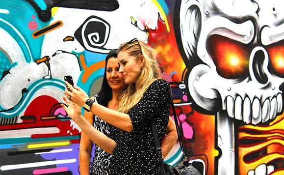 Participantes da festa Chilli Beans na Rua faz selfy diante de arte de rua  criada no local da festa